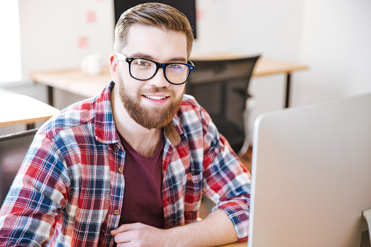 Happy handsome young man with bead in checkered shirt and glasses sitting on workplace and working with computer